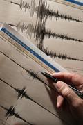 Ein Geowissenschaftler der Universität Jena studiert das im Geodynamischen Observatorium Moxa aufgezeichnete Seismogramm eines Nachbebens in Japan vom 14. März 2011, gegen 08.08 Uhr (MEZ). Darunter das Seismogramm des Hauptbebens vom 11. März 2011. Foto: Jan-Peter Kasper/FSU