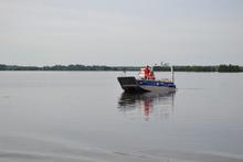 Mit Booten fährt das THW zum Deich, um die Sprengladung in den vorbereiteten Bohrlöchern anzubringen. Quelle: THW/Tommy Hoffmann